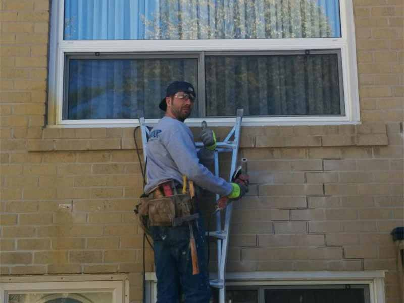 parging repair | PH Group Staff Working on ladder| Barrie Ontario