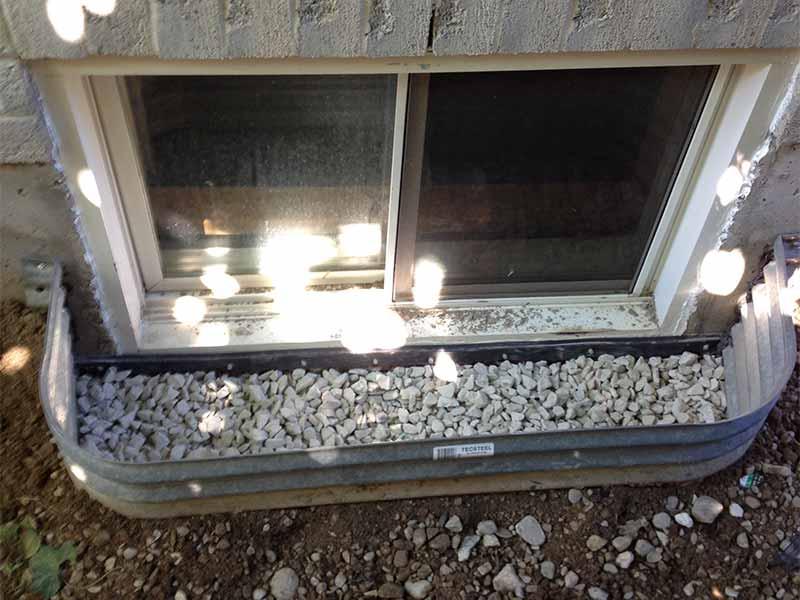 window well waterproofing with stones